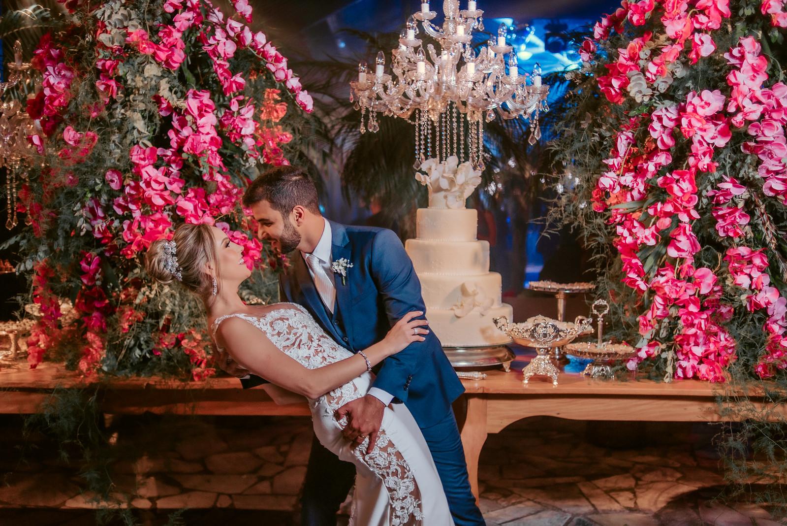 Noivos se olhando em frente ao bolo do buffet de casamento